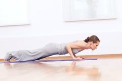 Donna che fa allungando esercitazione di yoga alla ginnastica di sport Immagine Stock