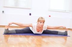 Donna che fa allungando esercitazione di yoga alla ginnastica di sport Immagini Stock