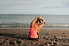 Donna che fa allungando esercizio alla spiaggia Fotografie Stock