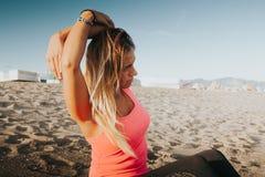 Donna che fa allungando esercizio alla spiaggia Fotografia Stock