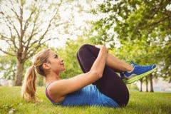 Donna che fa allungando esercizio mentre trovandosi nell'erba Fotografia Stock