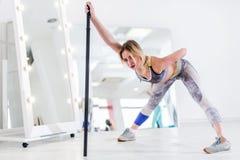 Donna che fa allungando esercizio per i tendini del ginocchio e parte posteriore che pendono il bilanciere di andata della tenuta fotografie stock