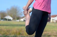 Donna che fa allungando esercizio prima del pareggiare Immagini Stock Libere da Diritti