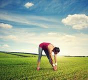 Donna che fa allungando gli esercizi ad all'aperto Fotografia Stock Libera da Diritti