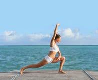 Donna che fa allungando gli esercizi dal mare Immagine Stock Libera da Diritti