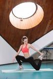 Donna che fa allungando gli esercizi nella palestra Immagine Stock Libera da Diritti