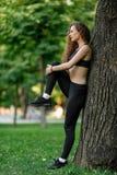 Donna che fa allungando gli esercizi prima dell'correre Fotografia Stock Libera da Diritti
