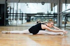 Donna che fa allungando gli esercizi sul pavimento Fotografie Stock