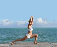 Donna che fa allungando gli esercizi sulla riva Fotografie Stock Libere da Diritti