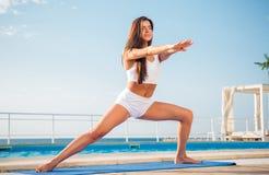 Donna che fa allungando gli esercizi sulla stuoia di yoga Immagini Stock Libere da Diritti