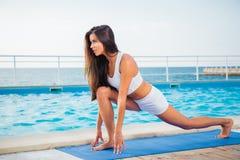 Donna che fa allungando gli esercizi sulla stuoia di yoga Fotografie Stock Libere da Diritti