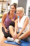 Donna che fa allungando le esercitazioni in ginnastica Immagine Stock Libera da Diritti