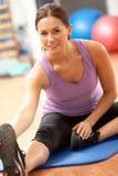 Donna che fa allungando le esercitazioni in ginnastica Fotografia Stock Libera da Diritti