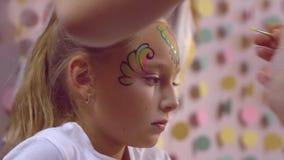 Donna che fa aquagrim sulla ragazza con la spazzola, vernice di carrozzeria sul fronte video d archivio