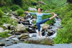 Donna che fa asana di yoga di Ashtanga Vinyasa all'aperto alla cascata fotografie stock