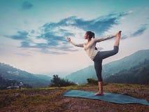 Donna che fa asana Natarajasana di yoga all'aperto sul tramonto immagine stock
