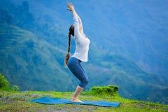 Donna che fa asana Utkatasana di yoga all'aperto immagini stock libere da diritti
