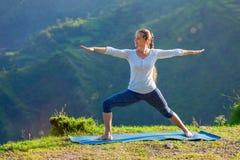 Donna che fa asana Virabhadrasana 2 di yoga - il guerriero posa all'aperto fotografia stock
