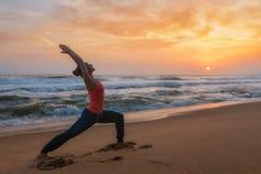 Donna che fa asana Virabhadrasana di yoga 1 posa del guerriero sulla spiaggia sopra fotografia stock
