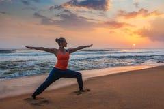 Donna che fa asana Virabhadrasana di yoga 1 posa del guerriero sulla spiaggia sopra immagine stock libera da diritti