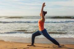 Donna che fa asana Virabhadrasana di yoga 1 posa del guerriero sulla spiaggia sopra immagini stock