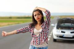 Donna che fa auto-stop davanti alla sua automobile rotta Immagini Stock