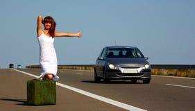 Donna che fa auto-stop su una strada principale Immagine Stock