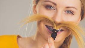 Donna che fa baffi dai capelli biondi Immagine Stock Libera da Diritti