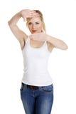 Donna che fa blocco per grafici sul suo fronte con le sue mani Fotografia Stock