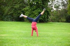 Donna che fa cartwheel Fotografie Stock Libere da Diritti