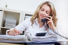 Donna che fa chiamata di telefono in ufficio Fotografia Stock Libera da Diritti