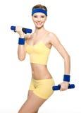 Donna che fa esercitazione di forma fisica con i dumbbells Immagini Stock