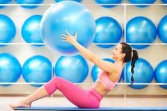 Donna che fa esercizio con la palla di forma fisica Immagine Stock