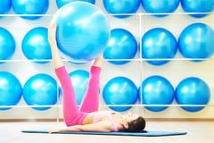 Donna che fa esercizio con la palla di forma fisica Fotografie Stock