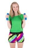 Donna che fa esercizio con le teste di legno blu in abiti sportivi Immagine Stock