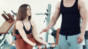 Donna che fa esercizio del bicipite con le teste di legno stock footage