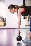 Donna che fa esercizio dell'oscillazione con un kettlebell Fotografia Stock