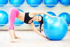 Donna che fa esercizio della palla di forma fisica di riscaldamento Fotografia Stock
