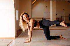 Donna che fa esercizio della plancia con le gambe allenamento di addestramento di concetto Immagini Stock