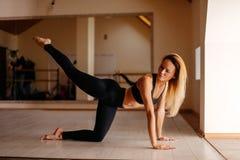 Donna che fa esercizio della plancia con le gambe allenamento di addestramento di concetto Fotografia Stock