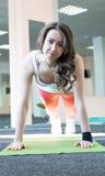 donna che fa esercizio della plancia in palestra o nell'yoga Immagini Stock