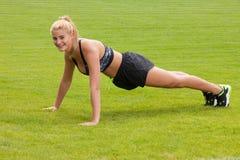 Donna che fa esercizio di allungamento di forma fisica all'aperto Immagine Stock