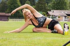 Donna che fa esercizio di allungamento di forma fisica all'aperto Fotografia Stock