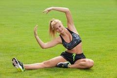 Donna che fa esercizio di allungamento di forma fisica all'aperto Immagini Stock