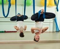 Donna che fa esercizio di yoga della mosca Immagine Stock