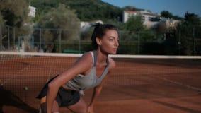 Donna che fa esercizio per le natiche della gamba sul campo da tennis archivi video