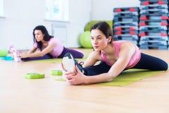 Donna che fa esercizio spaccato dell'incrocio che risolve i suoi muscoli abduttori e legamenti dell'anca Allungamento adatto dell Immagini Stock Libere da Diritti