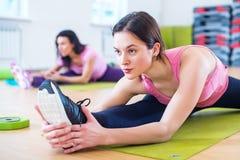 Donna che fa esercizio spaccato dell'incrocio che risolve i suoi muscoli abduttori e legamenti dell'anca Allungamento adatto dell Fotografia Stock