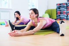 Donna che fa esercizio spaccato dell'incrocio che risolve i suoi muscoli abduttori e legamenti dell'anca Allungamento adatto dell Fotografia Stock Libera da Diritti