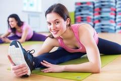 Donna che fa esercizio spaccato dell'incrocio che risolve i suoi muscoli abduttori e legamenti dell'anca Allungamento adatto dell Immagine Stock